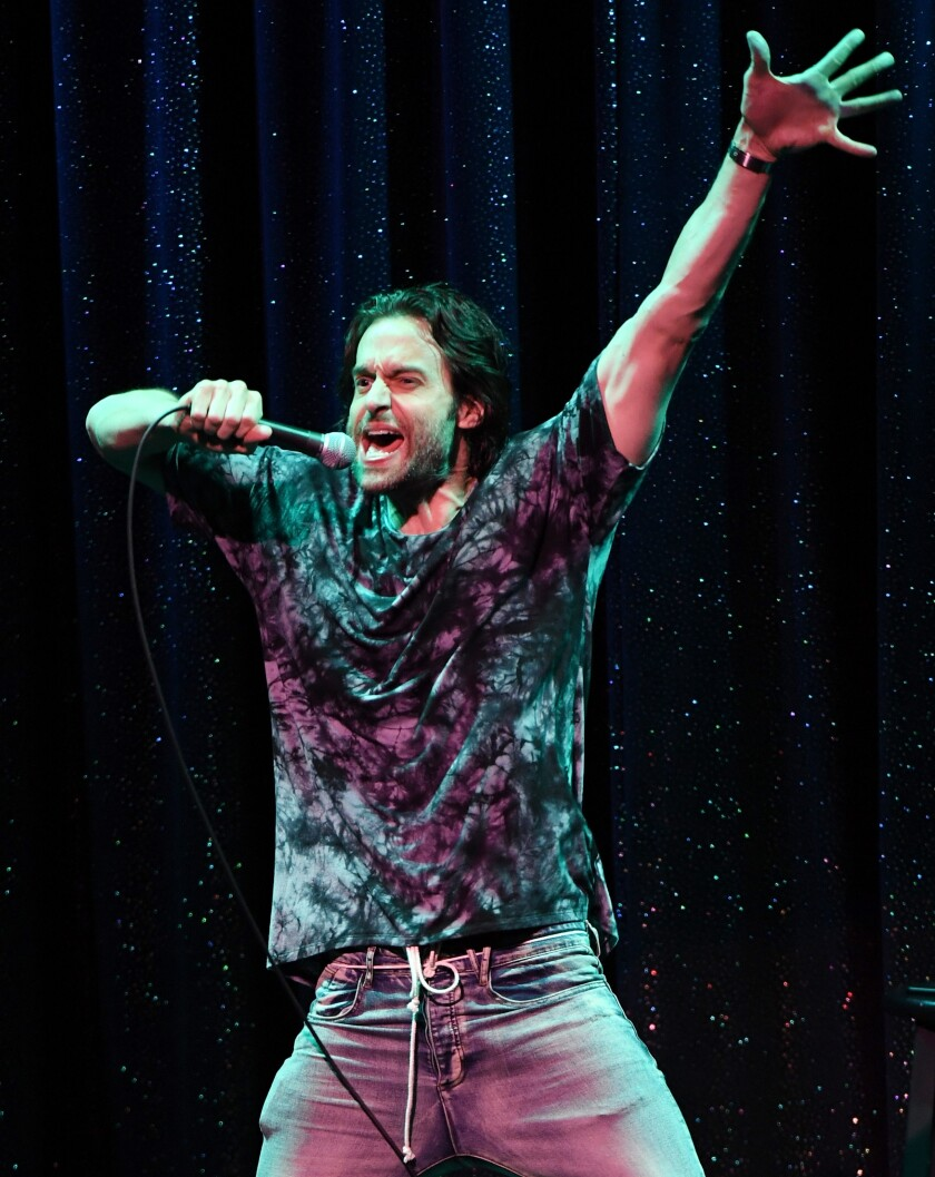 Chris D'Elia onstage holding a microphone