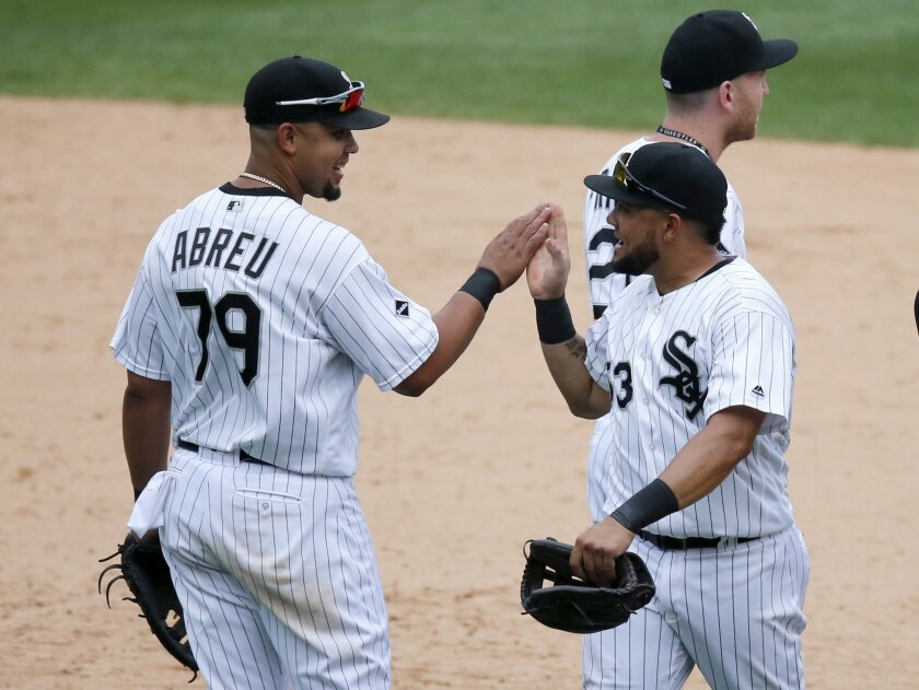Chicago White Sox's Jose Abreu (79) and Melky Cabrera celebrate the White Sox's 7-4 win over the Detroit Tigers after a baseball game Wednesday, Sept. 7, 2016, in Chicago. (AP Photo/Charles Rex Arbogast)
