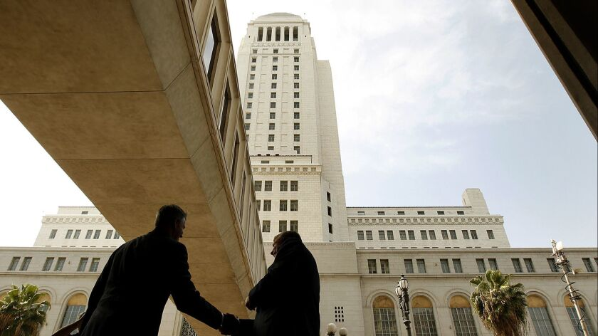 Two men shake hands next to Los Angeles City Hall.