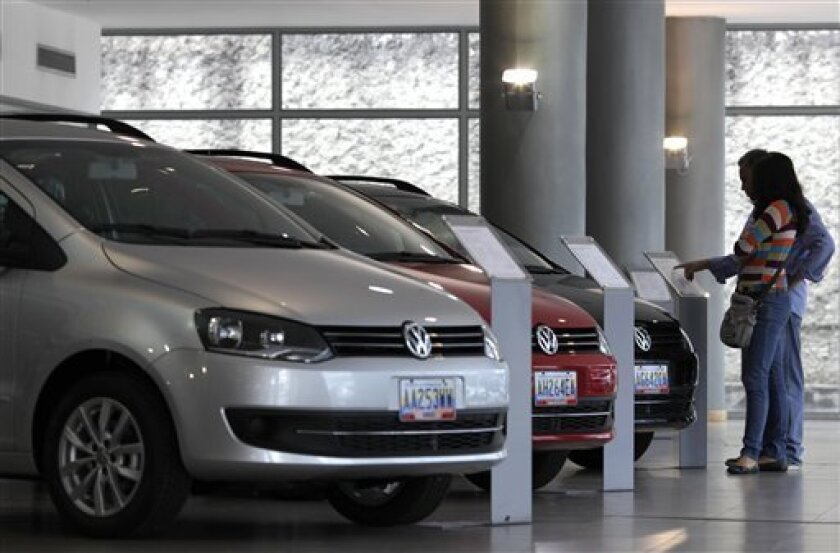 In this Feb. 1, 2013 photo, a couple looks at the price of a new vehicle that has already been sold, parked next to other already sold cars on display at a Volkswagen salesroom in Caracas, Venezuela. Venezuela may be the only country in the world where a new car becomes more expensive the instant it's driven off the dealership lot. The price reversal, many economists say, is the result of President Hugo Chavez's socialist-oriented economic controls. New cars have become so scarce that many showrooms sit nearly empty and would-be buyers must sign up on long waiting lists. (AP Photo/Ariana Cubillos)