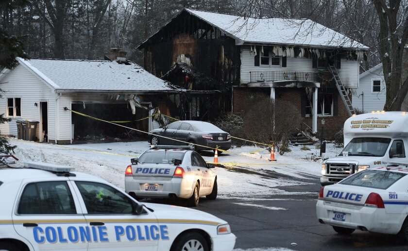 Law enforcement officials investigate a fatal fire, Wednesday, Feb. 10, 2016, in Colonie, N.Y. Police in upstate New York say bodies have been found in a house owned by a local police officer after firefighters responded to a fire at the home. (Skip Dickstein/The Albany Times Union via AP)  TROY, S