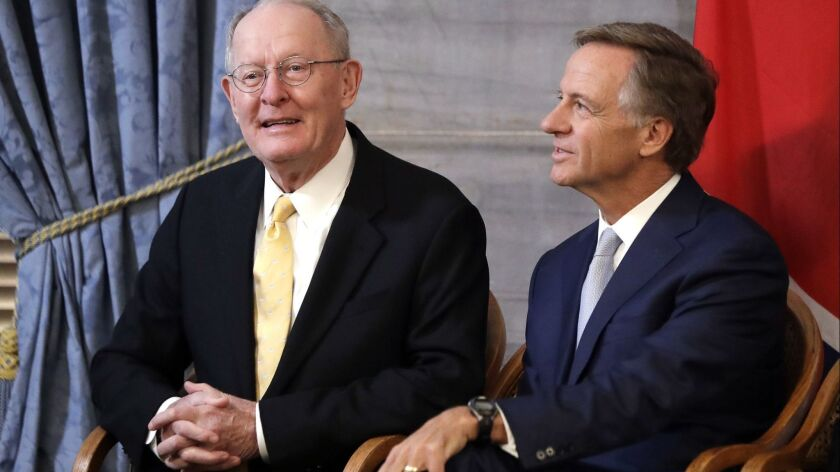 Sen. Lamar Alexander (R-Tenn.) left, sits with outgoing Tennessee Gov. Bill Haslam during a ceremony unveiling Haslam's official portrait in Nashville on Monday.