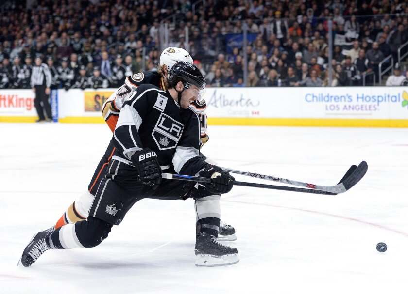 The Kings' Mike Richards attempts a backhand in front of the Ducks' Hampus Lindholm on Jan. 17 at Staples Center.