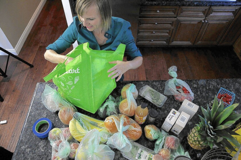 Burbank resident Tricia Carr unloads bags of groceries she ordered through delivery service Instacart. A new study says many consumers will keep using such services even after the pandemic ends.