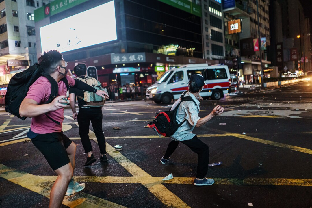 \Protester attack police vans with bricks as the vehicles pull out from the Mong Kok district of Hong Kong.