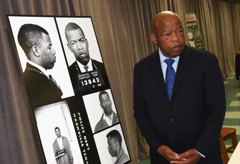 Rep. John Lewis views images in 2017 of his March 1963 arrest for leading a sit-in in Nashville.