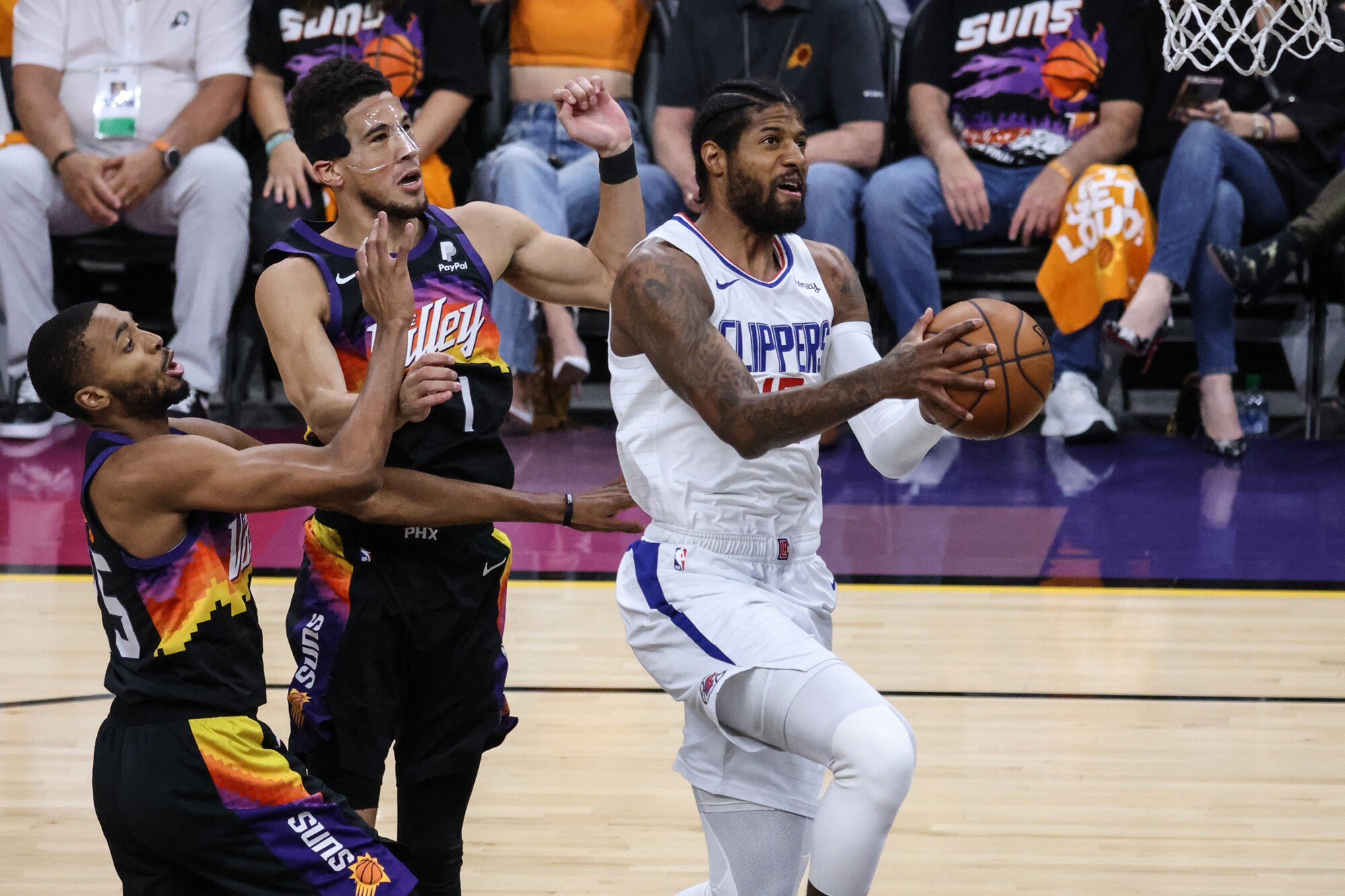 Clippers forward Paul George elevates past Suns guard Devin Booker and forward Mikal Bridges (25) for a layup during Game 5.