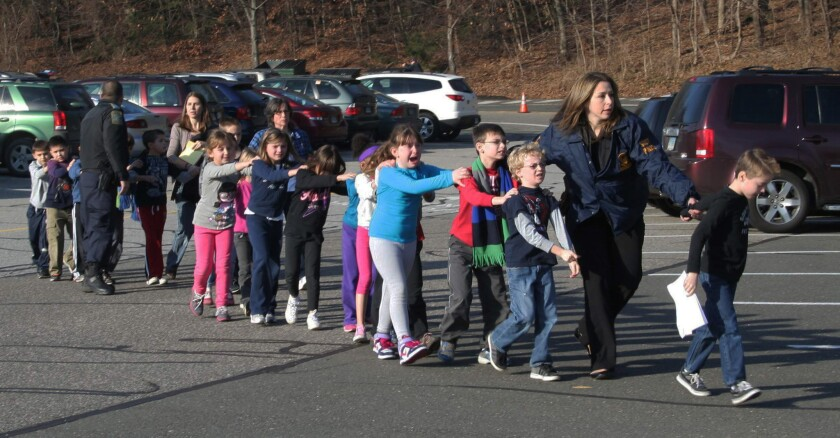 Connecticut State Police lead a line of children from the Sandy Hook Elementary School in Newtown, Conn., after a mass shooting at the school.