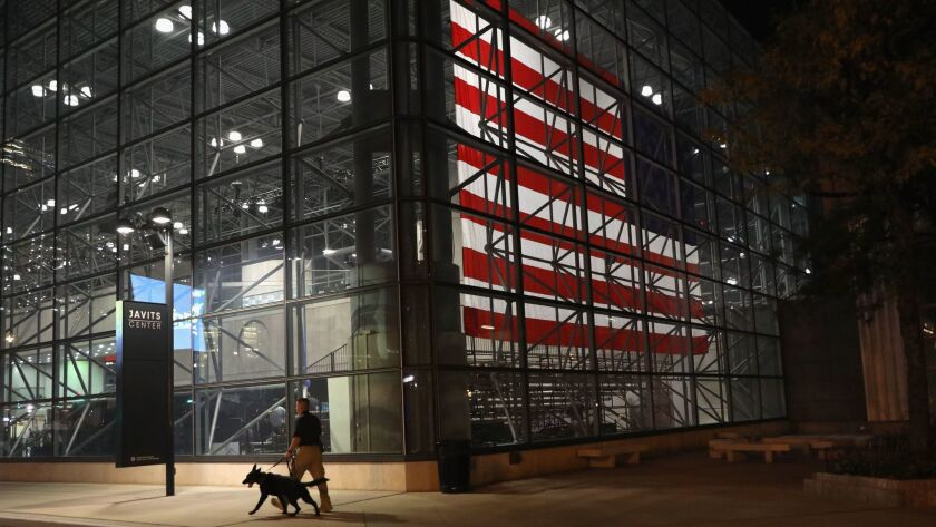 A U.S. Secret Service agent walks a bomb sniffing dog outside the Javits Center Monday in New York City.