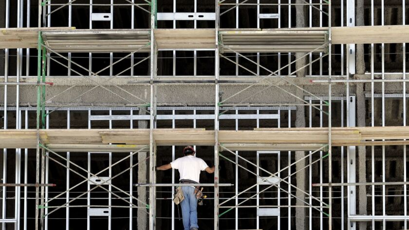 A worker helps build an apartment and retail complex in Nashville, Tenn., in 2017.