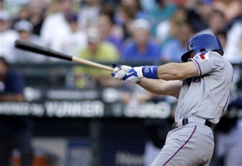 Texas Rangers' Michael Young hits a three-run home run in the third inning against the Seattle Mariners in a MLB baseball game Friday, July 10, 2009, at Safeco Field in Seattle. (AP Photo/Ted S. Warren)