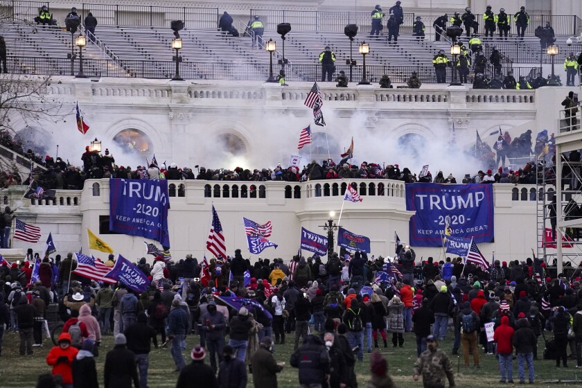 Rioters wave Trump 2020 flags outside the Capitol as smoke rises.