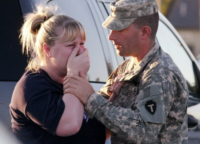 Sgt. Anthony Sills, right, comforts his wife as they wait outside the Fort Hood Army Base near Killeen, Texas on Thursday, Nov. 5, 2009. The Sills' 3-year old son is still in daycare on the base, which is in lock-down following a mass shooting earlier in the day. (AP Photo/Jack Plunkett)
