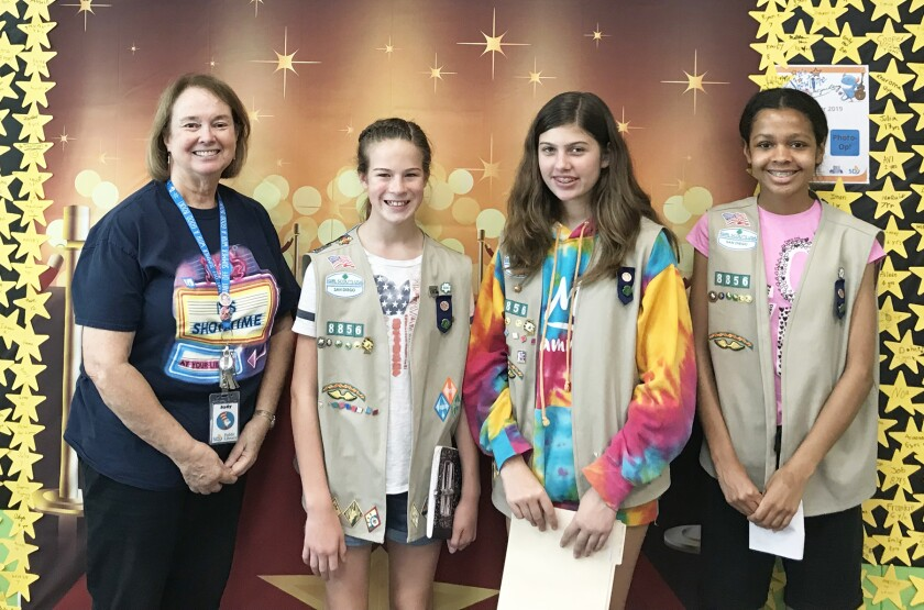 SDPL Branch Manager Judy Cunningham with Cadette Girl Scouts Amanda Lyons, Kaylee Johnson and Maya May.