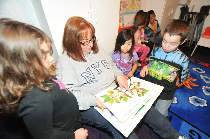Denise Sidney, of Sidney Family Day Care in Hesperia, reads to Ariana Sanchez, 5, left, Mya Mesa, 5, center right, and Nicklaus Gomez, 7.