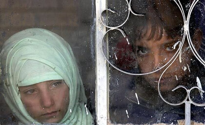 Iraqi children watch through a window as U.S. soldiers search their home.