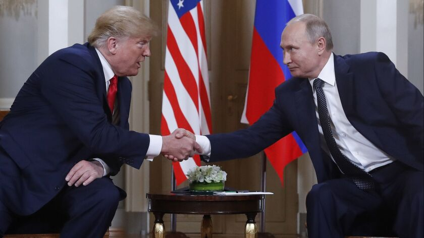 President Trump and Russian President Vladimir Putin greet each other at the beginning of a meeting at the Presidential Palace in Helsinki, Finland, on Monday.