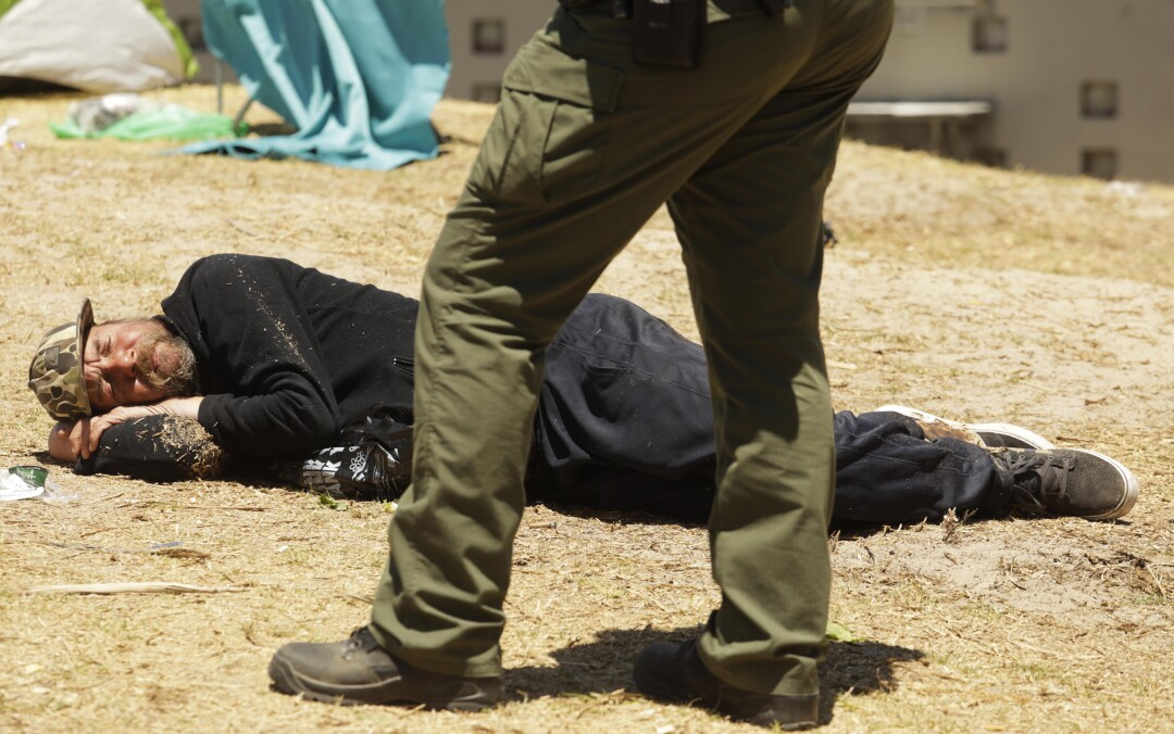 A homeless man lying on the ground with a deputy standing over him.