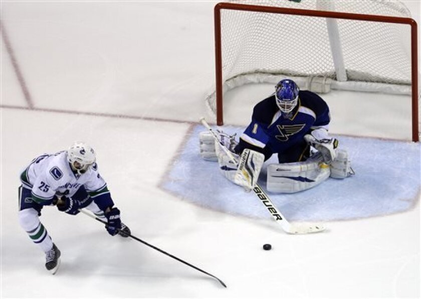 Vancouver Canucks' Andrew Ebbett, left, reaches for a loose puck as St. Louis Blues goalie Brian Elliott defends during the second period of an NHL hockey game Tuesday, April 16, 2013, in St. Louis. (AP Photo/Jeff Roberson)