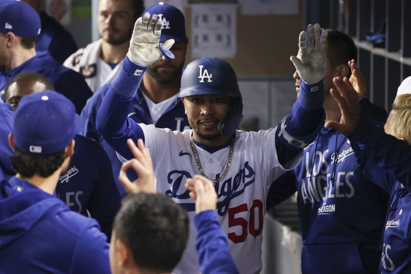 Dodgers outfielder Mookie Betts celebrates with teammates in the dugout.
