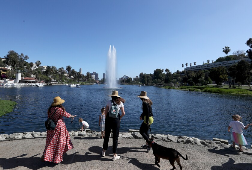 Visitors enjoy a sunny day on the banks of Echo Park Lake after the park reopened to the public.