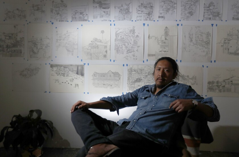 Artist Manuel Lopez framed by his drawings of hillside communities at his City Terrace studio.