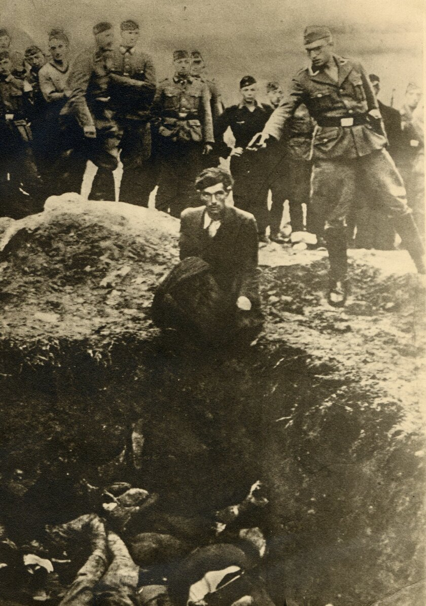 EDITORS NOTES GRAPHIC CONTENT - The photo taken between 1941 and 1943 near Vinnitsa, Ukraine, provided by the U.S. Holocaust Memorial Museum shows German soldiers of the Waffen-SS and the Reich Labor Service looking on as a member of an Einsatzgruppe prepares to shoot a Ukrainian Jew kneeling on the edge of a mass grave filled with corpses. The Simon Wiesenthal Center has identified dozens of former members of Nazi mobile death squads who might still be alive, and is pushing the German government for an investigation, The Associated Press has learned on Wednesday, Oct. 1, 2014. The Wiesenthal Center's top Nazi hunter, Efraim Zuroff, told the AP that in September he sent the German justice and interior ministries a list of 76 men and four women who served in the so-called Einsatzgruppen. (AP Photo/U.S. Holocaust Memorial Museum, courtesy of Sharon Paquette) NO ARCHIVE