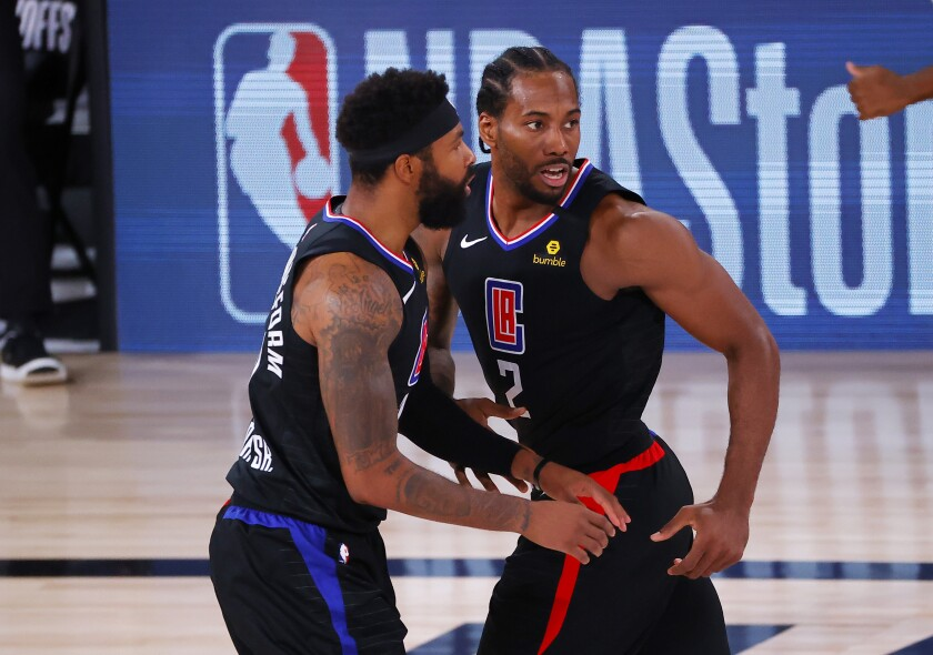 Los Angeles Clippers' Kawhi Leonard reacts with teammate Marcus Morris Sr., left, after hitting a jump shot.