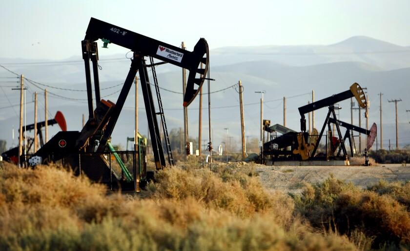 Oil rig pump jacks in a field.