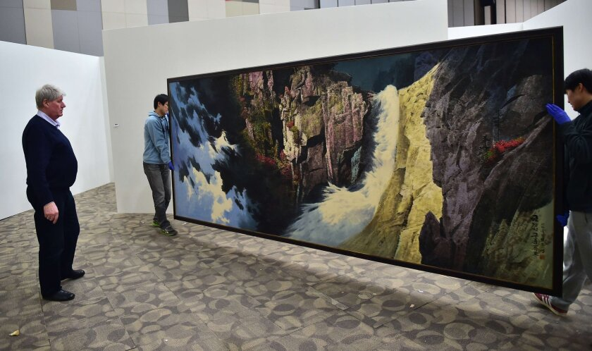 """Dutch collector Frans Broersen inspects a painting that's part of """"Hidden Treasures of North Korea Revealed,"""" a show he's curating in Goyang, South Korea."""