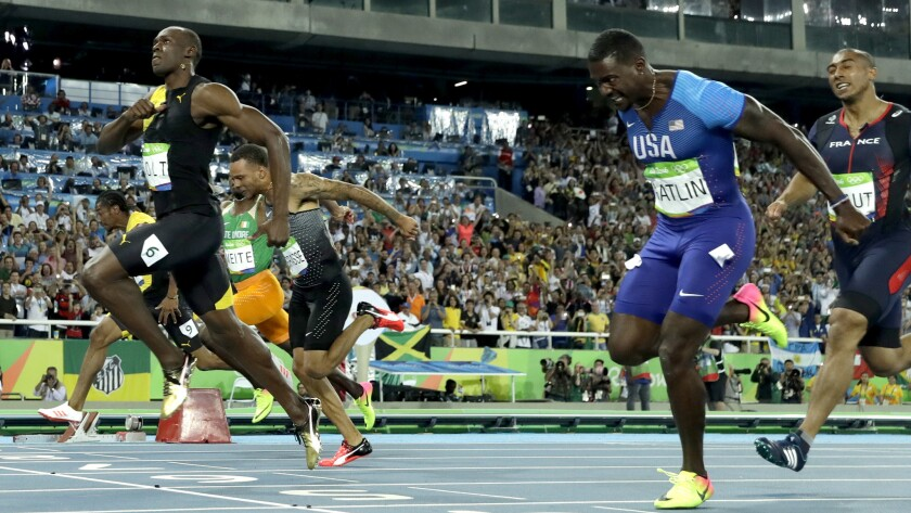 Jamaica's Usain Bolt, left, crosses the line ahead of American Justin Gatlin to win gold in the men's 100-meter final Sunday.