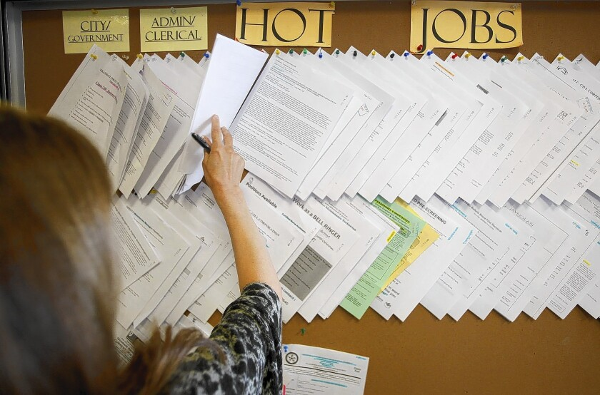 An unemployed worker checks the listings board at the Verdugo Jobs Center in Glendale.