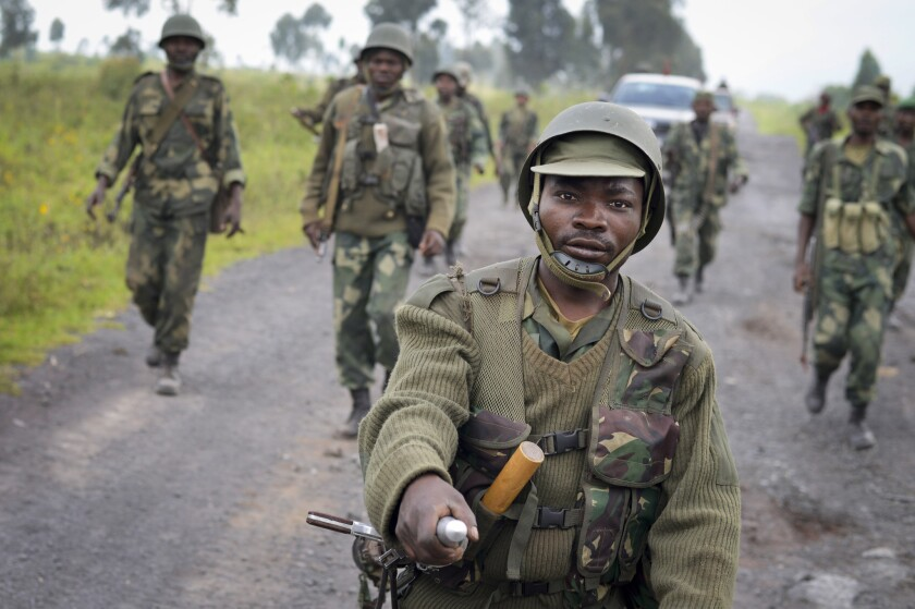 Congolese soldiers march through Kibumba on Monday after recapturing the town from M23 rebels over the weekend.