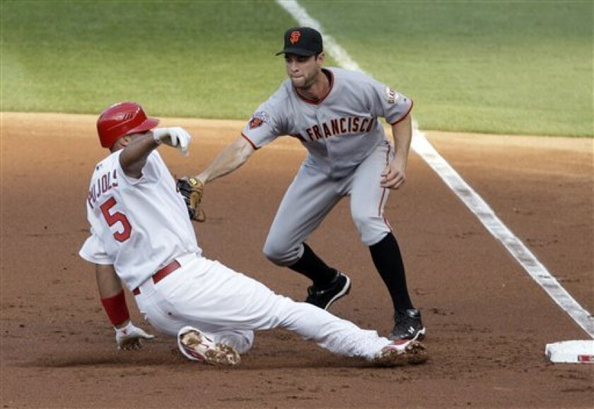 St. Louis Cardinals' Albert Pujols (5) is tagged out by San Francisco Giants first baseman Brandon Belt as he slides into first after trying to stretch his single in the first inning of a baseball game, Tuesday, May 31, 2011, in St. Louis.(AP Photo/Tom Gannam)