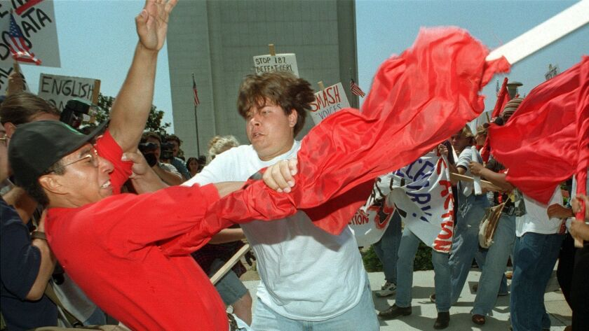 A pro-187 supporter, center with white shirt, gets in to a scuffle with an anti-187 protestor in Los Angeles on August 10, 1996.