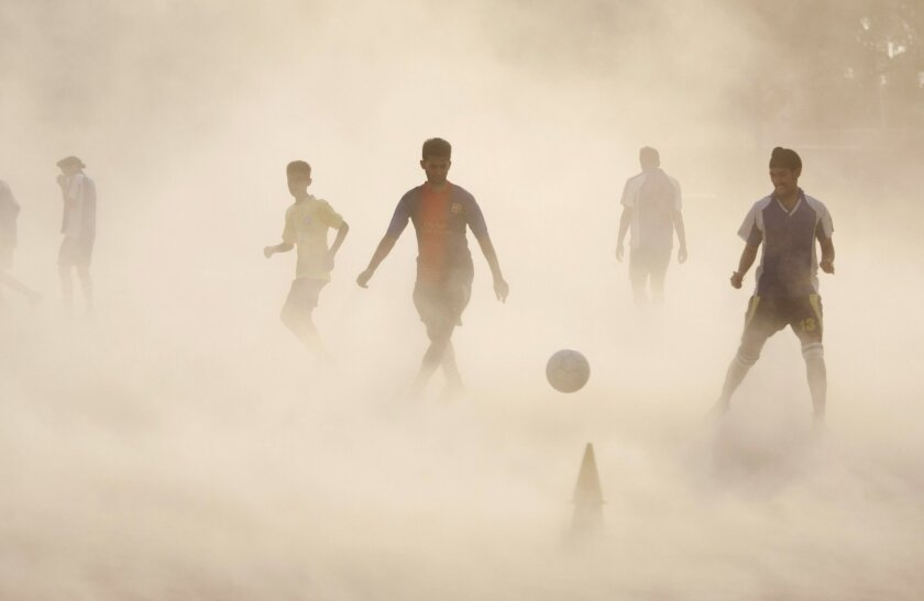 10ThingstoSeeSports - Aspiring young Indian soccer players continue with their practice during a dust storm in Jammu, India, Wednesday, June 11, 2014. Soccer fans around the world are gearing up to watch the Soccer World Cup that begins in Brazil on Thursday. (AP Photo/Channi Anand, File)