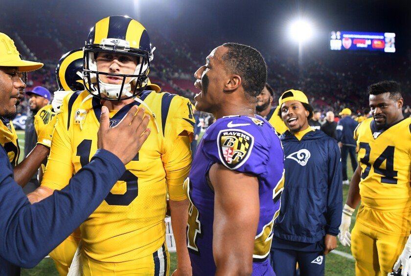 TheRavens' Marcus Peters talks to Rams quarterback Jared Goff as they leave the field after the game at the Coliseum on Monday.