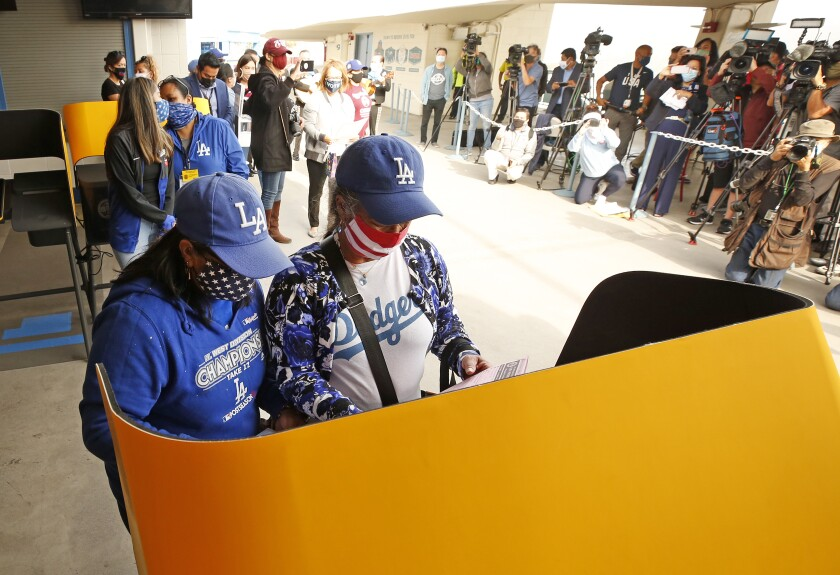 Two people in masks and Dodgers hats and shirts stand at a voting booth.