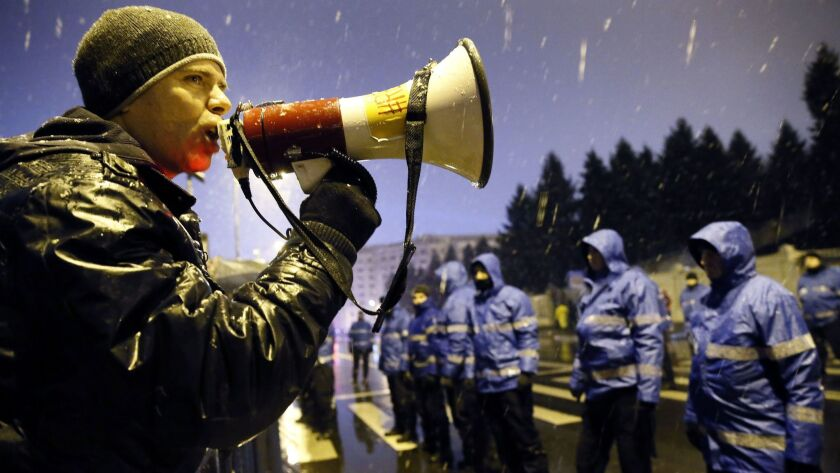 A Romanian demonstrator shouts slogans at riot police Dec. 17 in front of Parliament in Bucharest.