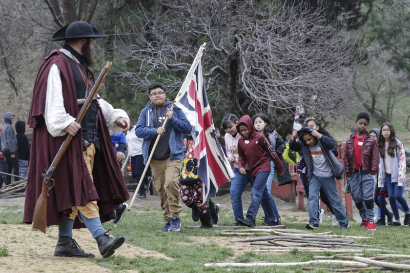 Michael Dougher, enacting the character of a rifleman teaching the colonists to fight for their liberties, leads a group of schoolchildren visiting Riley's Farm.