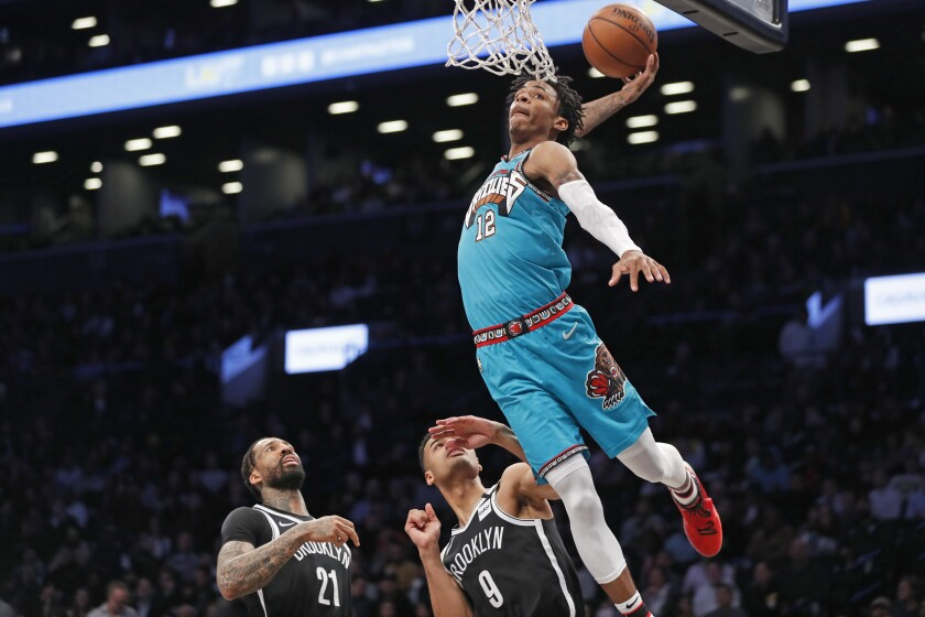 Memphis Grizzlies guard Ja Morant (12) goes up for a dunk as Brooklyn Nets forward Wilson Chandler (21) and Nets guard Timothe Luwawu-Cabarrot (9) watch from the floor during the second half of an NBA basketball game Wednesday, March 4, 2020, in New York. Morant, who had 28 points in then game, missed the whot, which bounced off the rim. The Grizzlies defeated the Nets 118-79. (AP Photo/Kathy Willens)