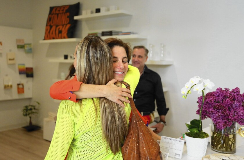 Suze Yalof Schwartz, right, hugs a participant following a class at her unplug meditation studio.