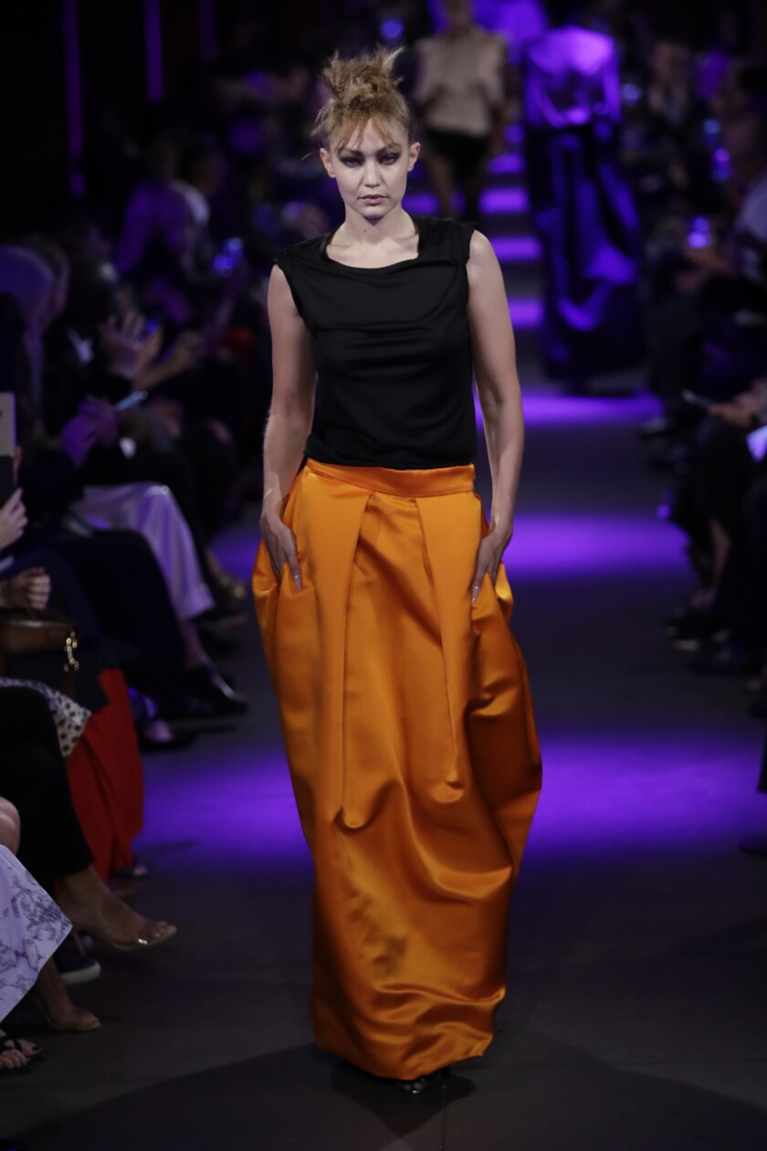 A look from the spring and summer 2020 Tom Ford runway collection: a simple black top and slouchy orange skirt