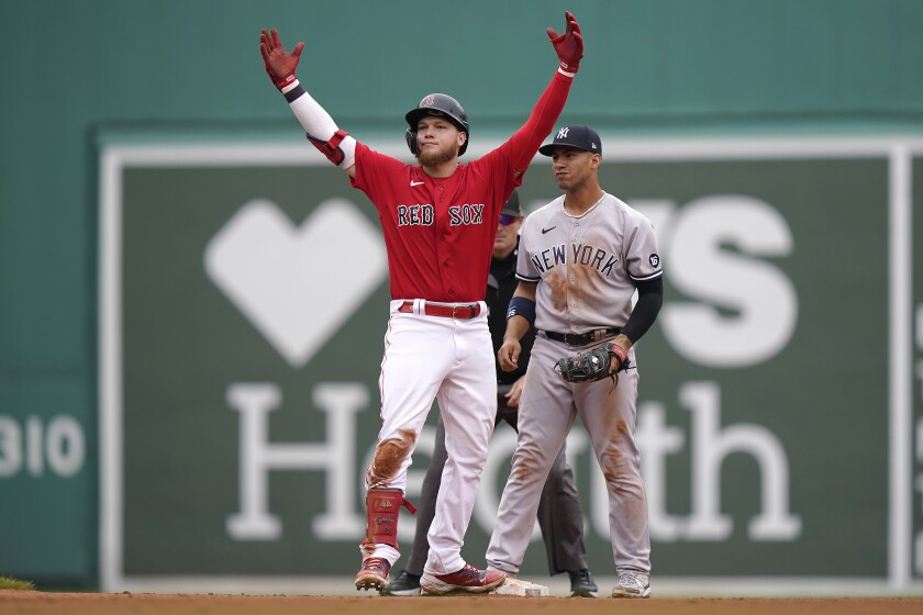 Boston Red Sox's Alex Verdugo raises his arms after arriving at second base on a double that broke up New York Yankees pitcher Domingo German's no-hitter in the eighth inning of a baseball game, Sunday, July 25, 2021, in Boston. Yankees' Gleyber Torres, right, looks on. (AP Photo/Steven Senne)