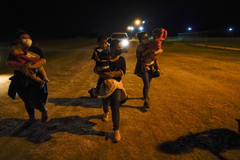 """FILE - In this May 11, 2021, file photo, migrant women carry children in the rain at an intake area after turning themselves in upon crossing the U.S.-Mexico border in La Joya, Texas. The U.S. Homeland Security Department says thousands of asylum-seekers whose claims were dismissed or denied under a Trump administration policy that forced them to wait in Mexico for their court hearings will be allowed to return for another chance at humanitarian protection. The Associated Press has learned that registration begins Wednesday, June 23, 2021 for asylum-seekers who were subject to the """"Remain in Mexico"""" policy and either had their cases dismissed or denied for failing to appear in court. (AP Photo/Gregory Bull, File)"""