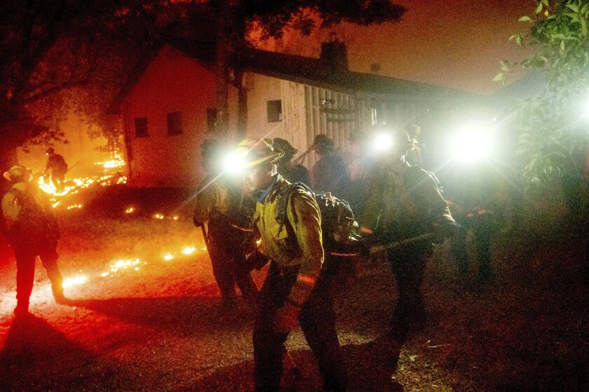 A crew works to save a home as the Bear fire chars the Berry Creek area of Butte County