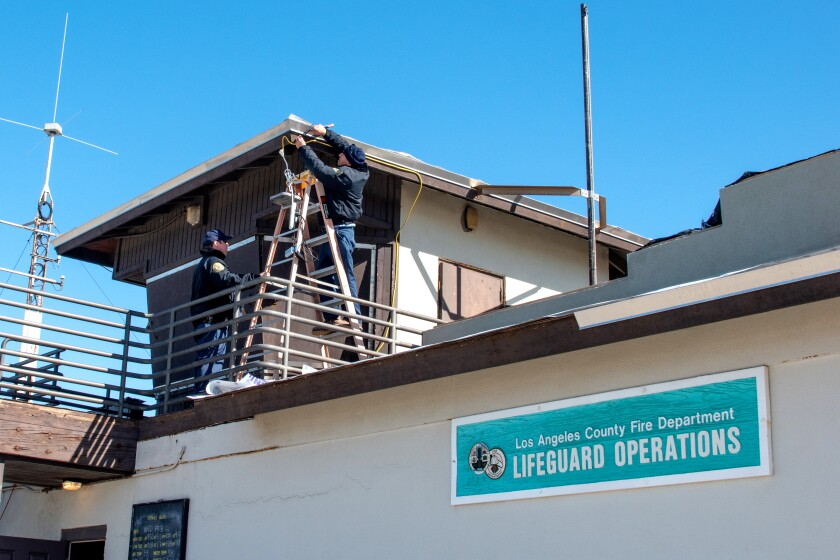 Workers with the Los Angeles County Department of Beaches and Harbors install strobe lights on a building at Torrance Beach. The lights are part the new Beach Emergency Evacuation Lights System, or BEELS, designed to alert deaf and hard-of-hearing beachgoers to emergencies at the coast.