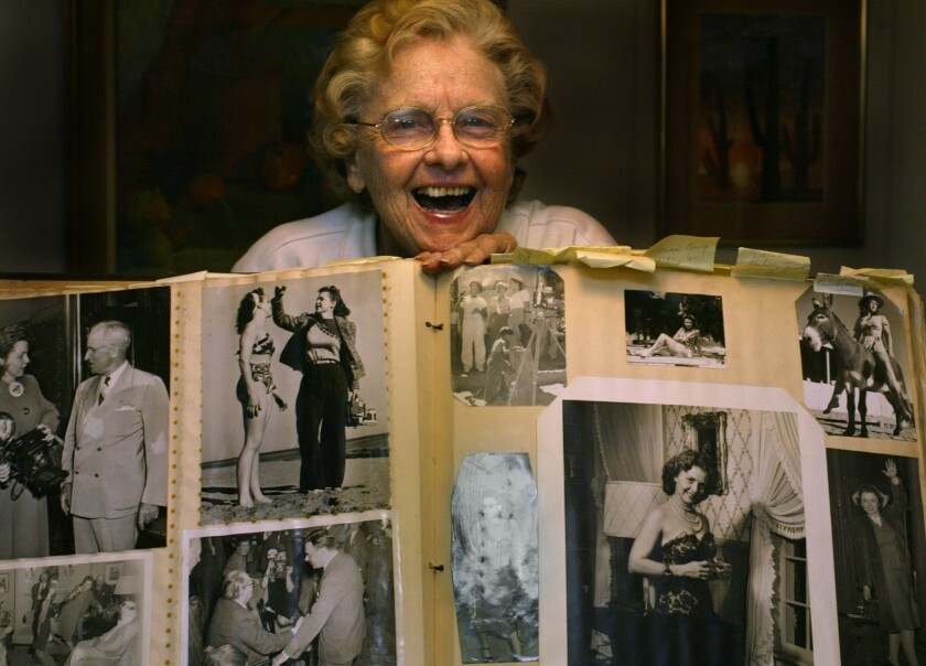Helen Brush Jenkins, a pioneering news photographer in the early 1940s at the now defunct L.A. Daily News, holds up a scrapbook of her work for a Times profile in 2005. She died Wednesday at age 94.