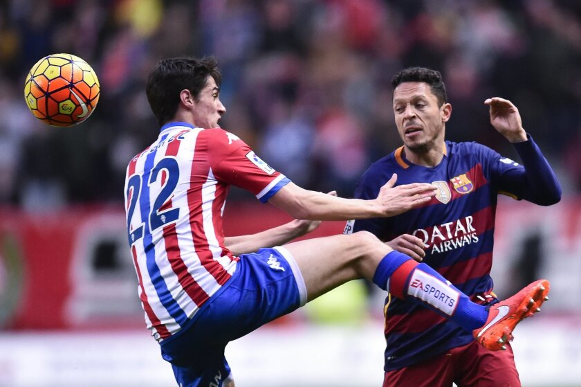 Sporting de Gijon's  Pablo Peres, left, duels for the ball with FC Barcelona's Adriano Correia during their Spanish La Liga soccer match between Sporting de Gijon and FC Barcelona, at El Molinon stadium, in Gijon, northern Spain, Wednesday, Feb.17, 2016. (AP Photo/Alvaro Barrientos)