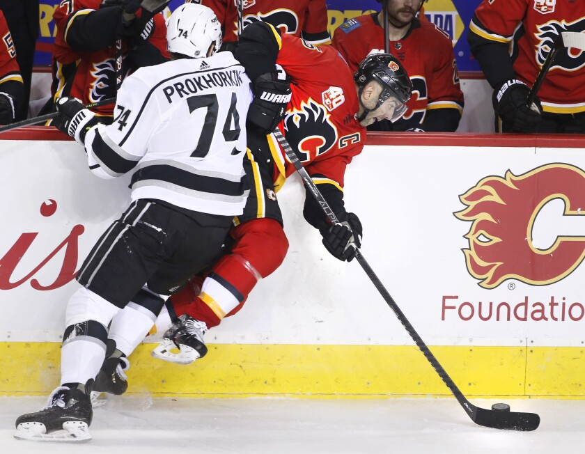 The Kings' Nikolai Prokhorkin hits the Flames' Mark Giordano into the boards during the second period Saturday night.